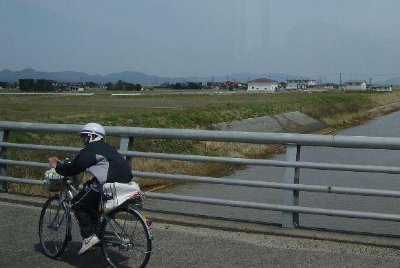 奥に見えるのが多分中国山脈。ジャージにヘルメットで自転車を乗る中学生(?)。田舎を感じる瞬間。